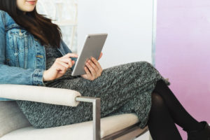 Woman sitting in waiting room looking at tablet