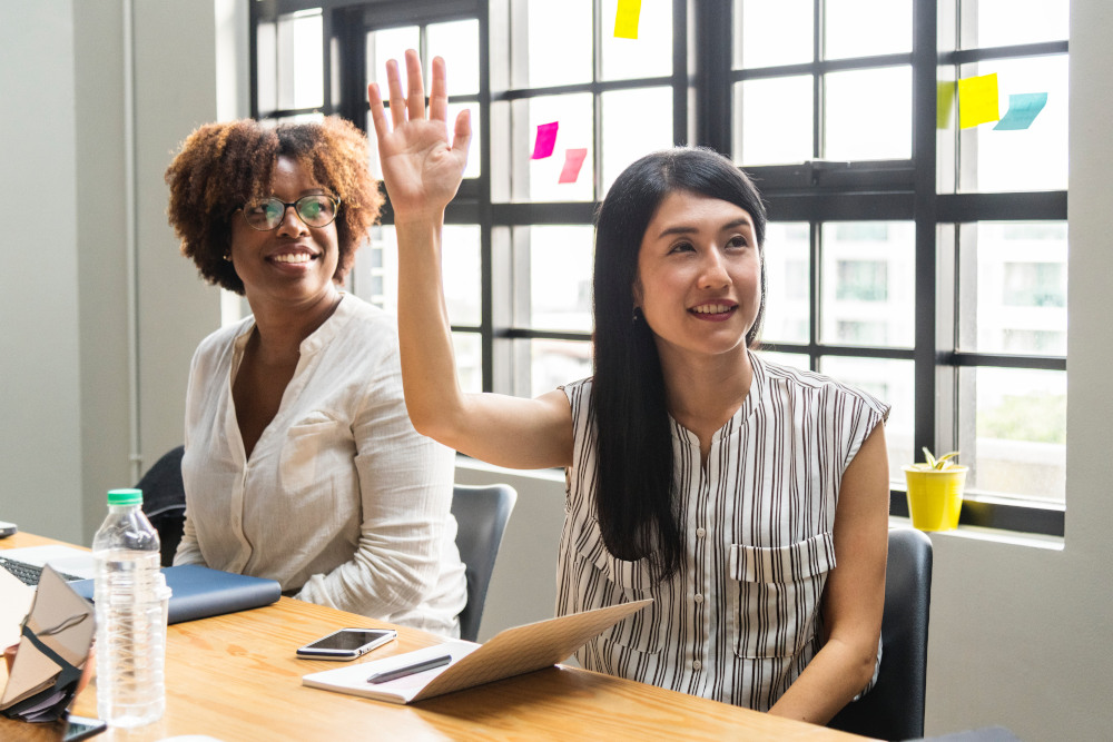 2 women in meeting asking questions