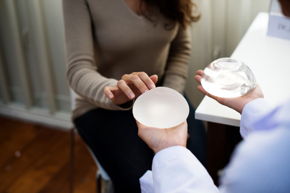 Woman looking at her breast implant options with her surgeon.