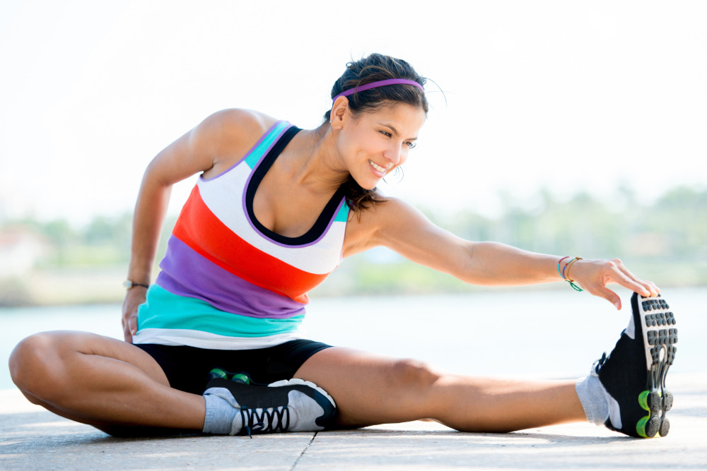 Fit woman doing stretching exercises outdoors and smiling.